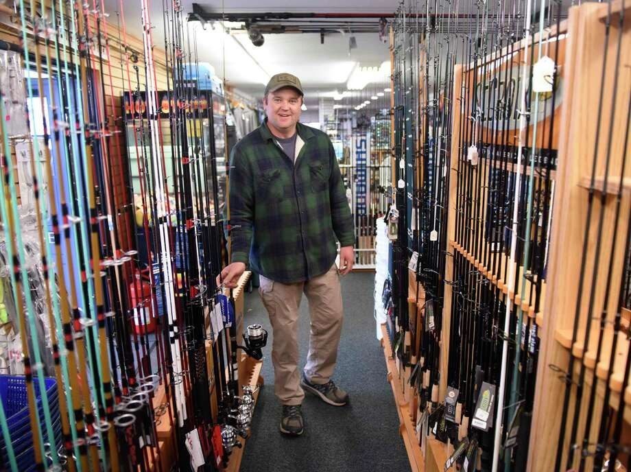 Store owner William Ingraham shows a selection of fishing rods available at The Sportsman's Den in the Cos Cob section of Greenwich on Wednesday. Connecticut Gov. Ned Lamont declared Wednesday the start of the fishing season as a measure to prevent the spread of the coronavirus by eliminating large crowds that typically accompany opening day. Photo: Tyler Sizemore / Hearst Connecticut Media / Greenwich Time