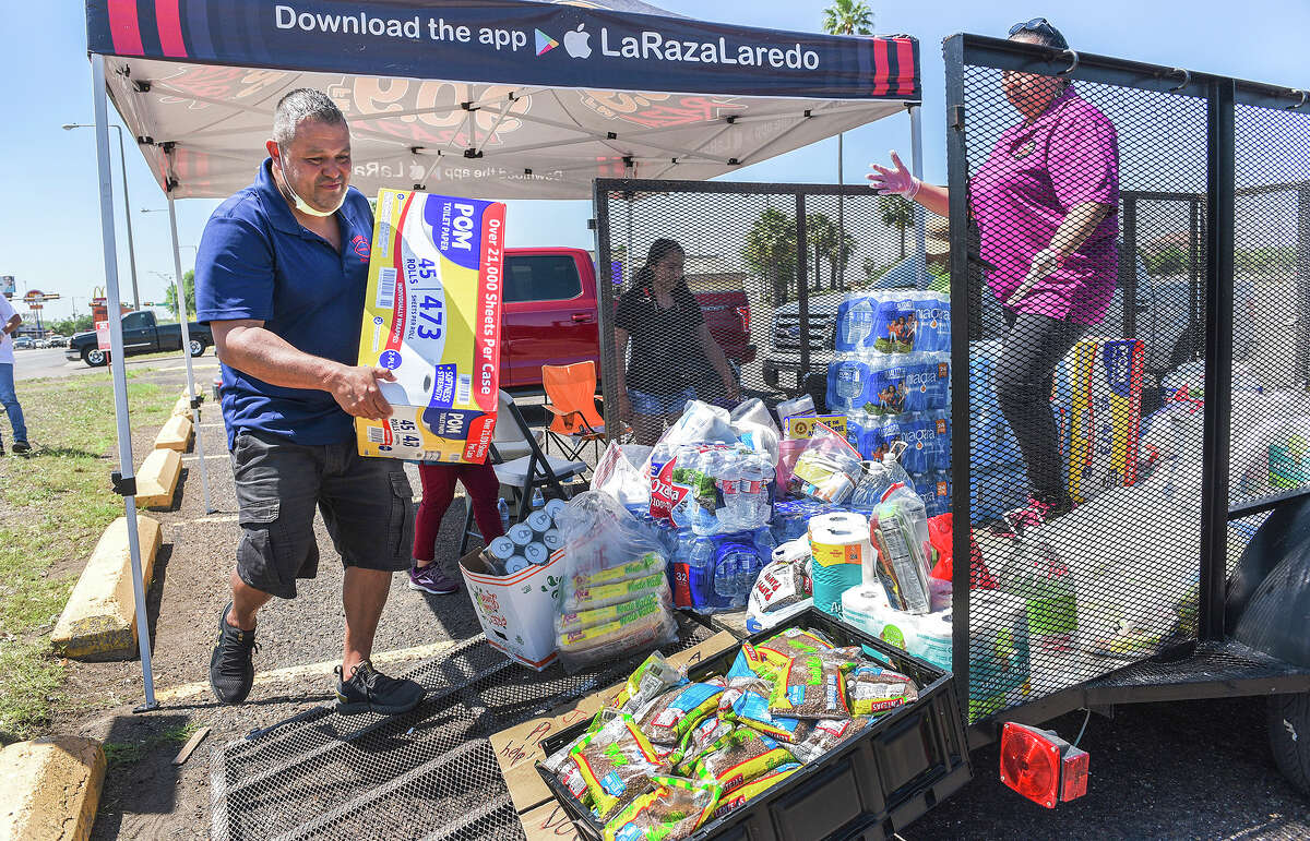 Fishers of Men Foods member Rafael Garcia and helper Sara Navarro arrange a trailer of donated items, Wednesday, Mar. 25, 2020, during a supply drive at the Big Lots Saunders location parking lot. The items will be disinfected and given to the elderly with little or no supplies.