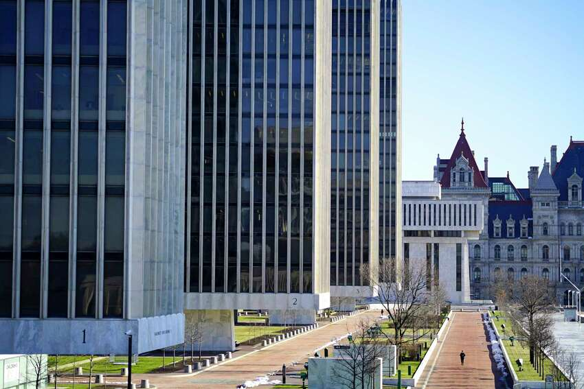 Times Union meteorologist Jason Gough says the sun will make a return appearance on Wednesday, April 1, 2020. In this photograhy, two people have the Empire State Plaza all to themselves on Thursday morning, March 26, 2020, in Albany, N.Y. (Paul Buckowski/Times Union)