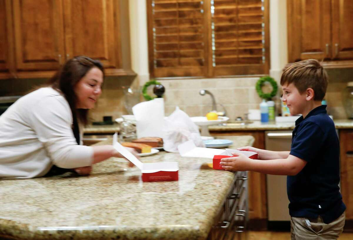 Jimmy Sloan, 9, laughs with his mom Janna as he grabs a cookie that had been delivered to their Houston home with the family is in self quarantine.