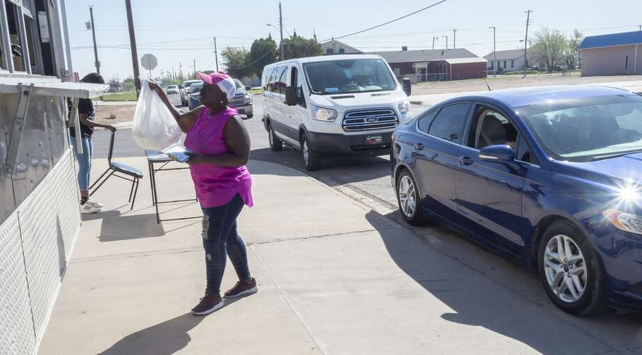 Volunteer Tammy Noble hands out plates of food outside The Electric Flava Cafe 03/26/2020 as they help serve beef tacos, beans and rice to give out to area children as part of a free lunch program owner Meleka McGee and other volunteers have been doing the past two weeks. Friday will be the final day they will hand out meals. Tim Fischer/Reporter-Telegram Photo: Tim Fischer/Midland Reporter-Telegram