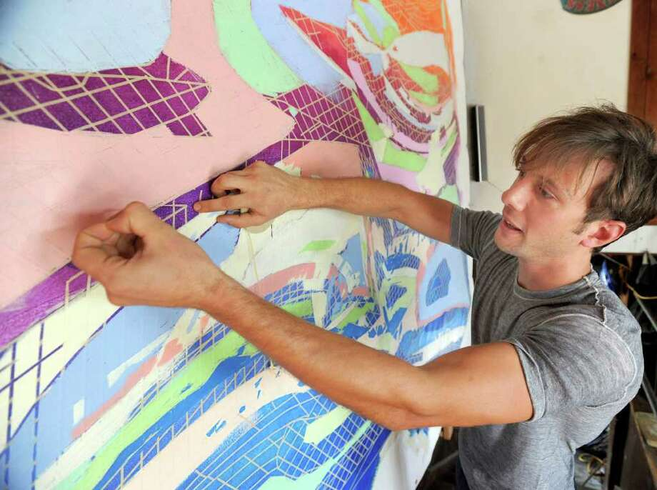 Jon Olivieri works on a canvas in his studio in Danbury. He drew inspiration for this painting from sedimentary rock formations he studied online. Photo taken Tuesday, August 17, 2010. Photo: Carol Kaliff / The News-Times