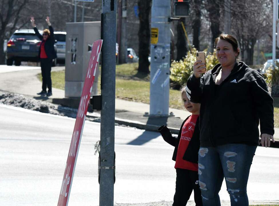 Shaker Road Elementary first-grader Kennedy Pielo, 7, is joined by her mom, Heather, as they cheer during a parade in support of school staff, students and family on Thursday, March 26, 2020, at the corner of Albany Shaker Road at Osborne in Colonie, N.Y. (Will Waldron/Times Union)