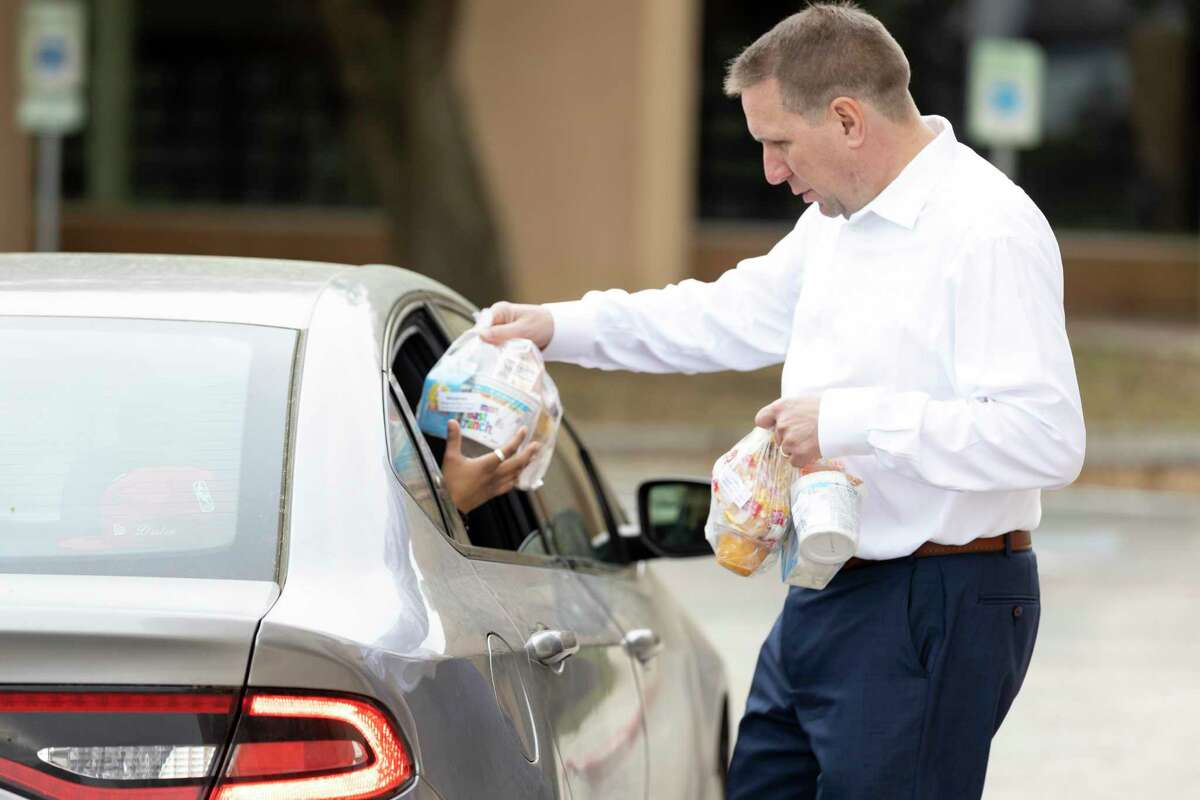 Conroe ISD Superintendent Curtis Null assists with the distribution of packed lunches and breakfast at Conroe High School, Tuesday, March 17, 2020. Conroe ISD prepared over 10,000 meals in response to school closures due to COVID-19.