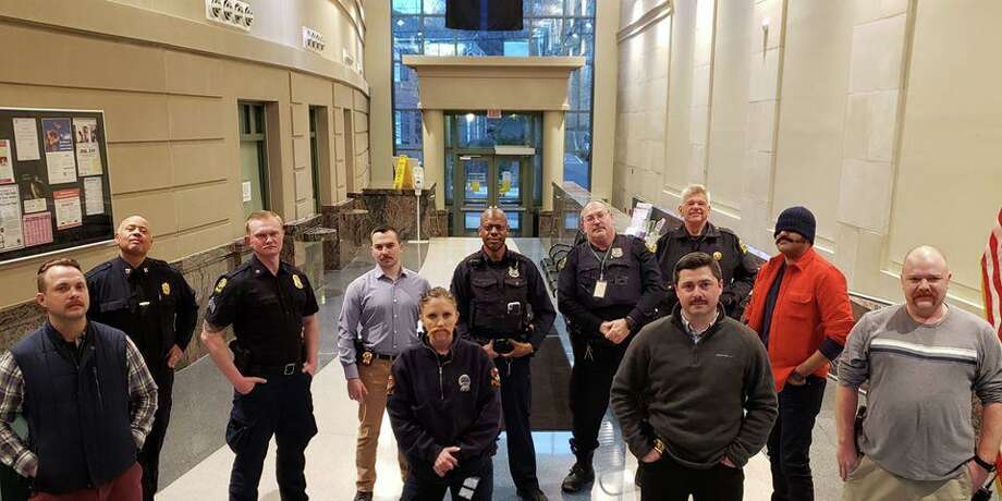 The newly shorn officers of the Greenwich Police Department — which is curtailing beards because they do not fit well with masks during the coronavirus outbreak — show off their mustaches at police headquarters. Det. Aran Santilli, center, with a fake mustache, was showing her solidarity. Photo: / GPD