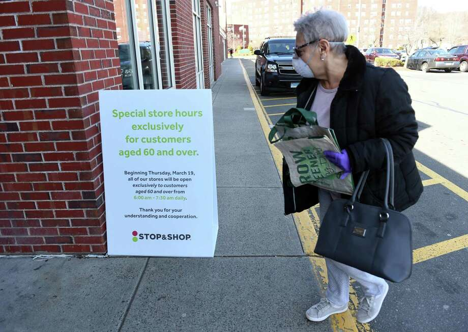 Lenore Mancusi of East Haven looks at a sign advertising shopping hours for customers over 60 at the Stop & Shop grocery store in East Haven March 22, 2020. Photo: Arnold Gold / Hearst Connecticut Media / New Haven Register