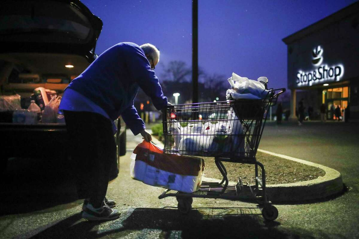 Customer Joseph Nathan loads toilet paper into the trunk of his car after shopping at a Stop & Shop supermarket that opened special morning hours to serve people 60 and older due to coronavirus concerns, March 20, 2020, in Teaneck, N.J.