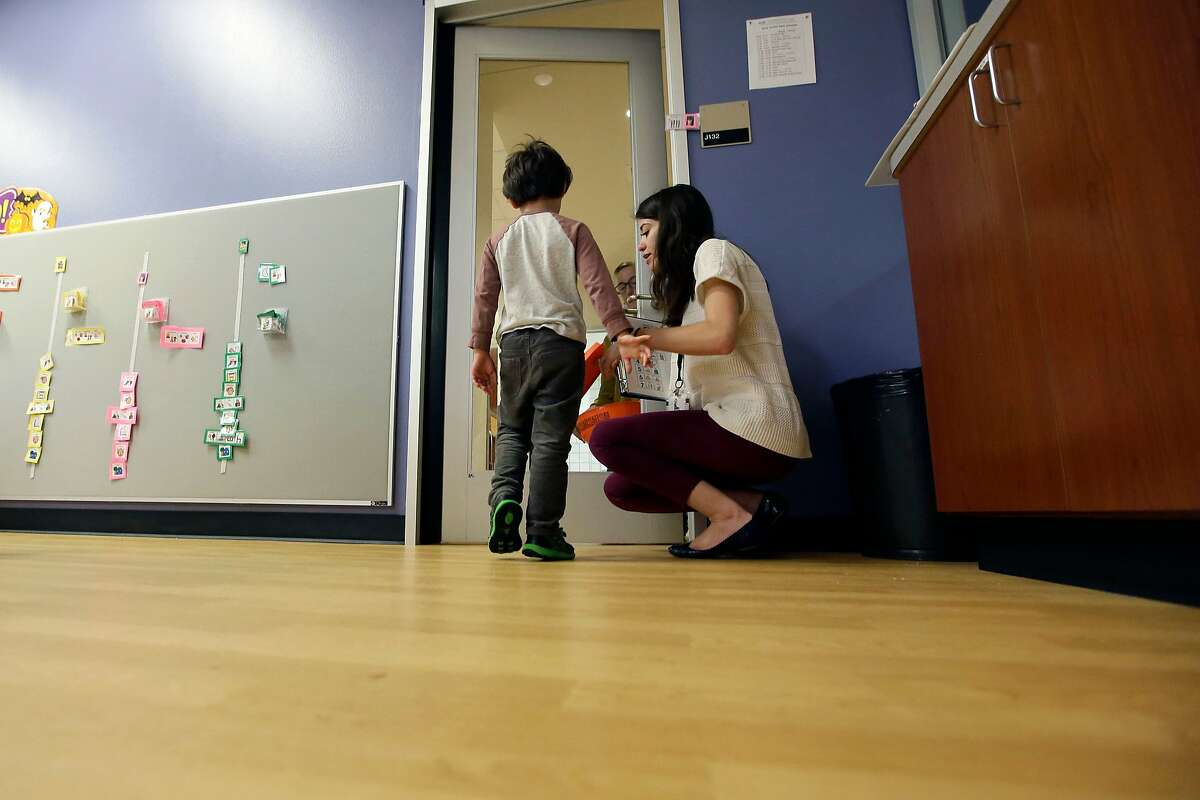 FILE - In this Monday, Oct. 24, 2016 file photo, Megan Krail helps a 4-year-old boy with Autism Spectrum Disorder practice trick-or-treating at The University of Texas at Dallas' Callier Center for Communication Disorders preschool class in Dallas. According to a report released by the Centers for Disease Control and Prevention on Thursday, March 26, 2020, about 1 in 54 U.S. children were identified as having autism in 2016. That's up from 1 in 59 children in 2014, and from 1 in 68 children in both 2010 and 2012. The study focused on 8-year-old children. (AP Photo/LM Otero)
