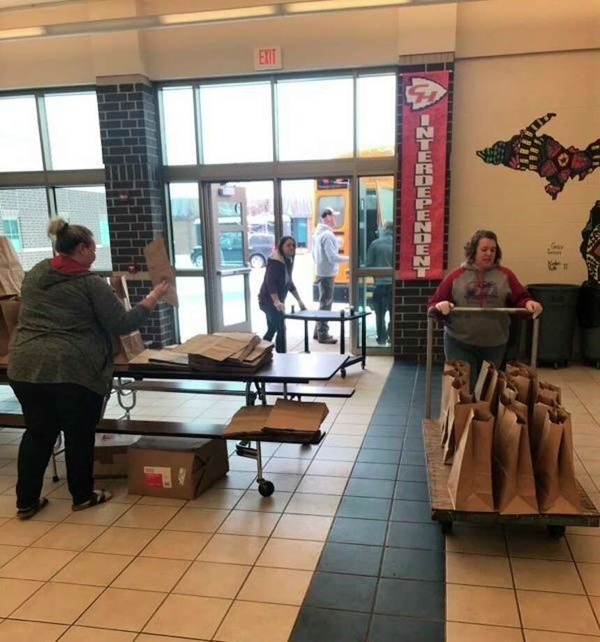 CHSD staff members bring bags of food out to the buses before delivery. The school district began its delivery service March 16. (Courtesy photo)