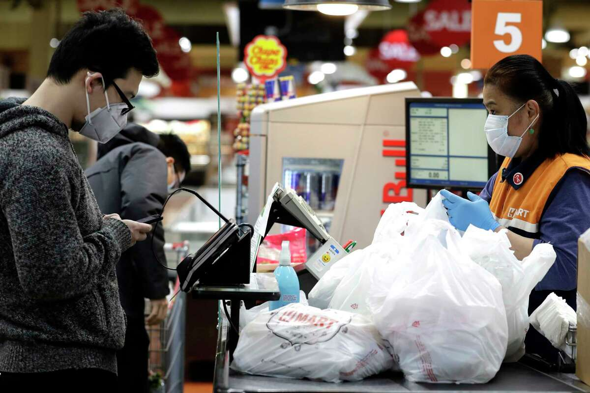 A cashier works behind a plexiglass shield at a Super H Mart grocery store in Niles, Ill., Thursday, March 26, 2020.