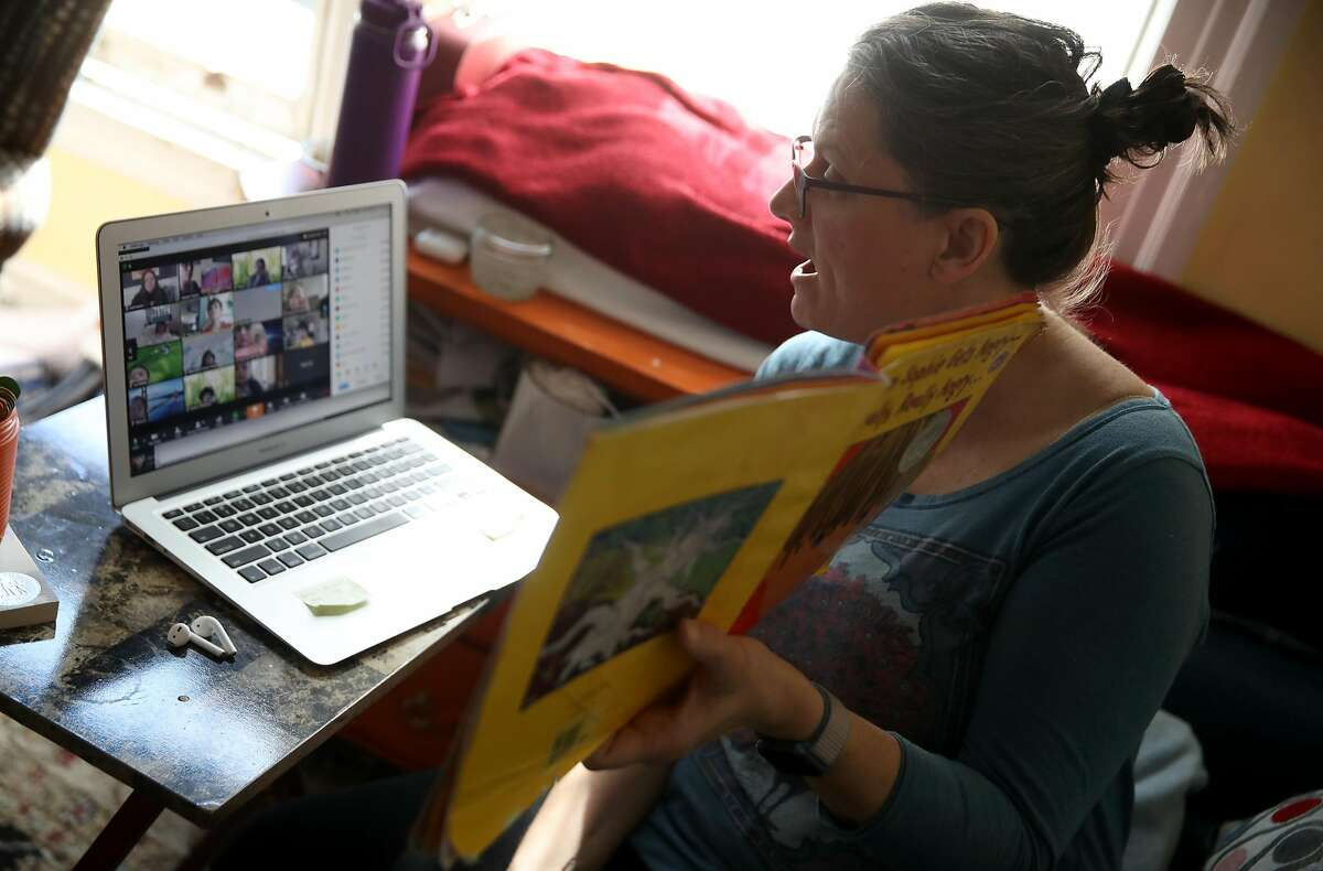 FILE - Leanne Francis, first grade teacher at Harvey Milk Civil Rights Academy, conducts an online class from her living room on March 20, 2020 in San Francisco, Calif.