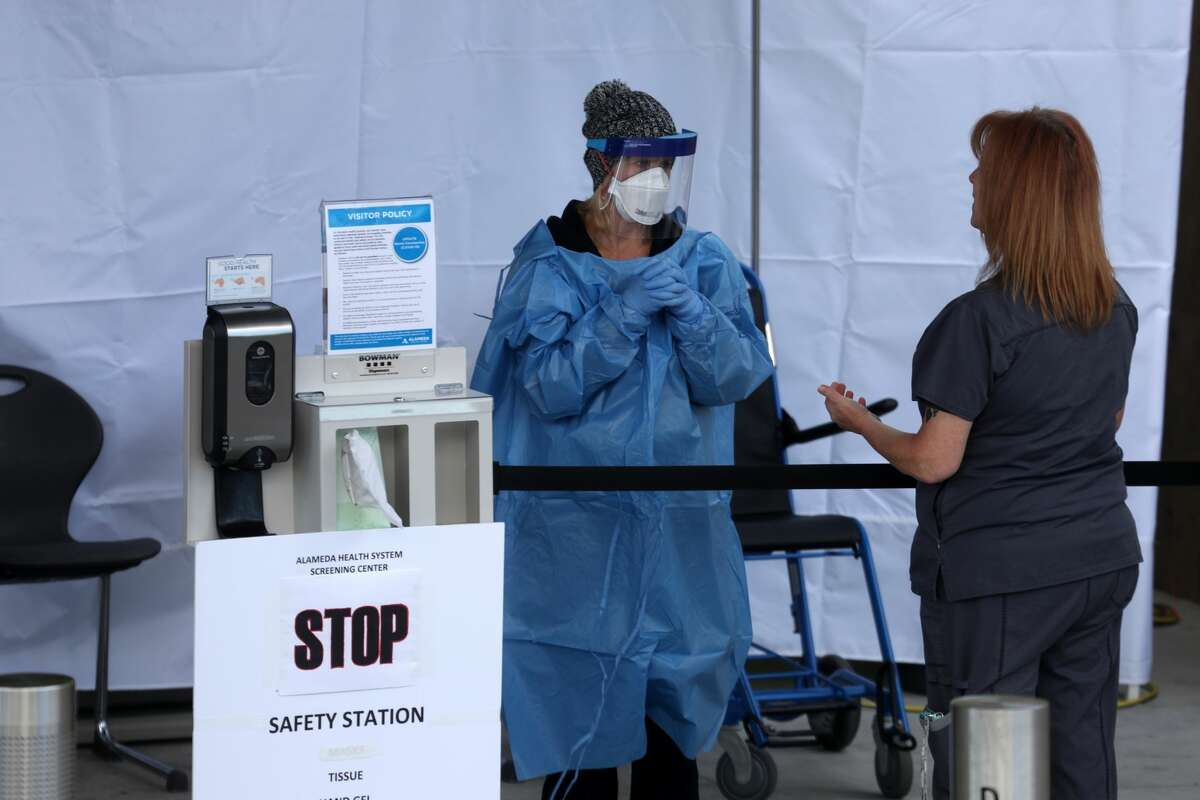Health care professionals screen people entering the emergency room at Highland Hospital on March 26, 2020 in Oakland.