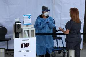 Healthcare professionals screen people entering the emergency room at Highland Hospital on March 26, 2020 in Oakland, California. Dozens of health care workers with Alameda Health System staged a protest to demand better working conditions and that proper personal protective equipment be provided in the effort to slow the spread of COVID-19.
