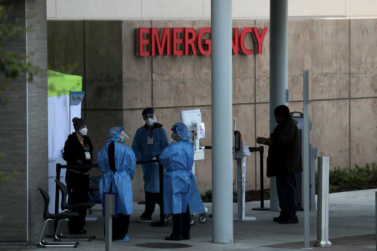 Health care professionals screen people entering the emergency room at Highland Hospital on March 26, 2020 in Oakland, California. Dozens of health care workers with Alameda Health System staged a protest to demand better working conditions and that proper personal protective equipment be provided in the effort to slow the spread of COVID-19.
