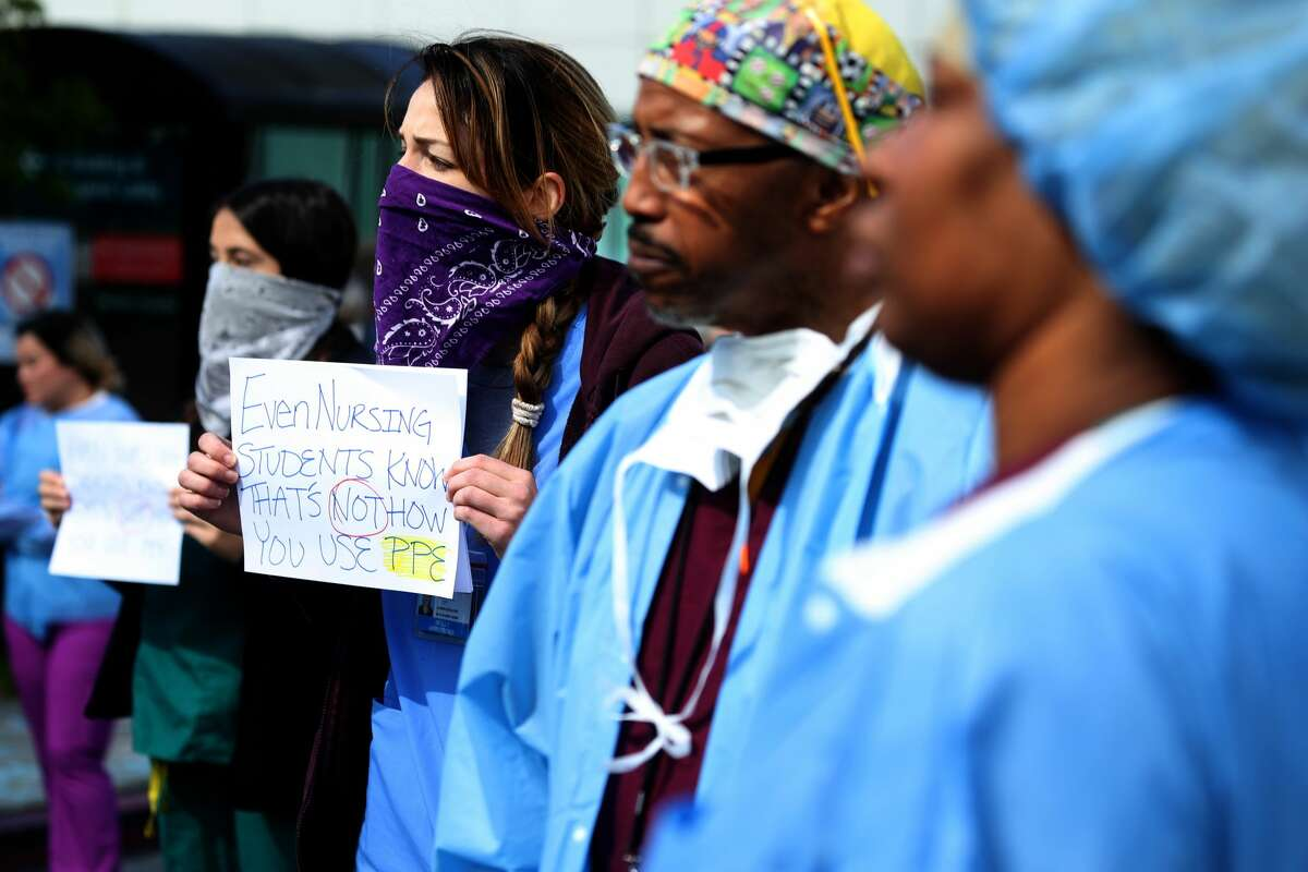 Alameda Health System nurses, doctors and workers hold signs during a protest in front of Highland Hospital on March 26, 2020 in Oakland, California. Dozens of health care workers with Alameda Health System staged a protest to demand better working conditions and that proper personal protective equipment be provided in the effort to slow the spread of COVID-19.