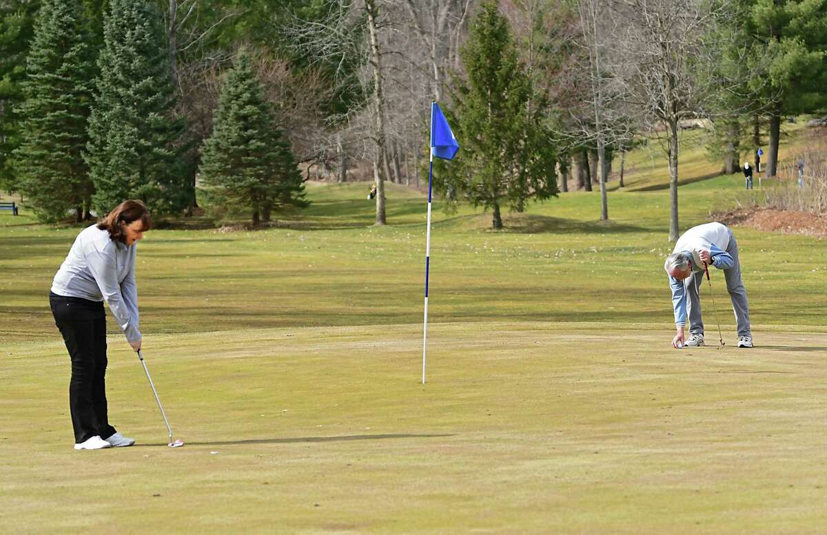 Diane Blake of Latham plays golf with her boyfriend Rich Lansing at Mill Road Acres Golf Course on Thursday, March 26, 2020 in Latham, N.Y. Many Capital Region courses that were open have now been ordered to close until at least April 29. (Lori Van Buren/Times Union)