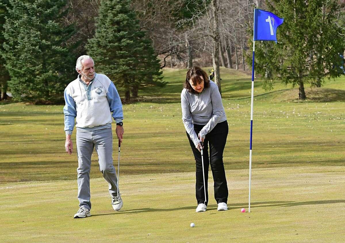 Diane Blake de Latham fait un putt alors que son petit ami Rich Lansing regarde au terrain de golf Mill Road Acres le jeudi 26 mars 2020 à Latham, New York.Ce parcours est ouvert maintenant et bientôt d'autres parcours de la région seront également ouverts avec des restrictions. (Lori Van Buren / Times Union)