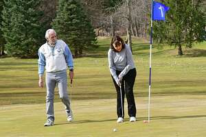 Diane Blake of Latham makes a putt as her boyfriend Rich Lansing watches at Mill Road Acres Golf Course on Thursday, March 26, 2020 in Latham, N.Y. This course is open now and soon other area courses with be open as well with restrictions. (Lori Van Buren/Times Union)
