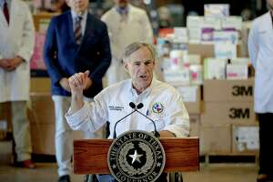Texas Gov. Greg Abbott gestures to boxes of personal protective equipment during a press conference about the state's response to the coronavirus. (Nick Wagner/Austin American-Statesman via AP)