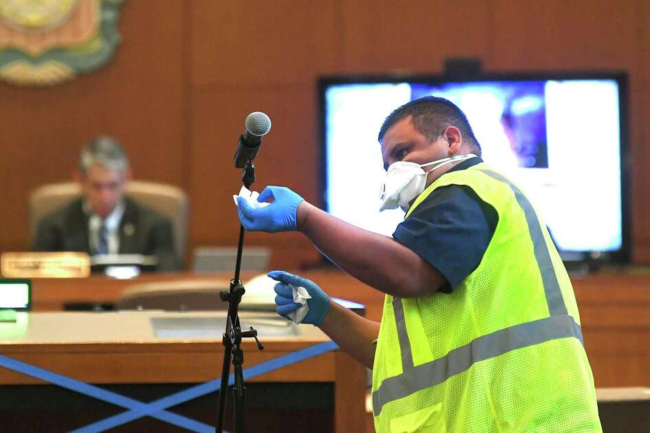 David Torres wipes down the microphone between speakers during a San Antonio City Council special meeting to vote on Mayor Ron Nirenberg's stay-at-home order to battle the coronavirus on Thursday, March 26, 2020.