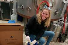 Kendall Gosma fills bottles with hand sanitizer. So far, Cranker's Brewery has produced more than 50 gallons of the new product. (Courtesy photo)