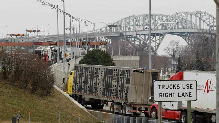 Vehicles wait to cross the Blue Water Bridge in Port Huron to Sarnia, Ontario, on March 18. The Canada-U.S. border is closed to nonessential traffic in both directions to help contain the coronavirus. Those who need to cross it, will no longer be able to pay with cash. (AP Photo/Paul Sancya) / Copyright 2020 The Associated Press. All rights reserved