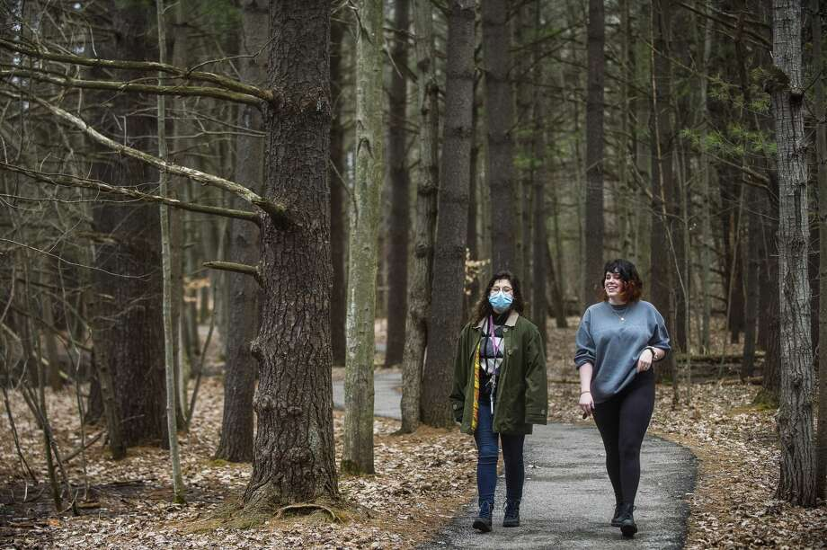 Taylor Propp, left, and Kai Klingbeil, right, both 21, stroll along a trail Thursday, March 26, 2020 at Chippewa Nature Center. Although the visitor center is closed, all trails at the nature center remain free and open to the public. (Katy Kildee/kkildee@mdn.net) Photo: (Katy Kildee/kkildee@mdn.net)