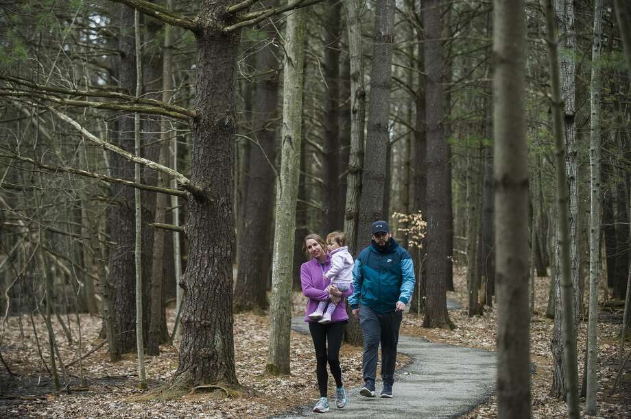 FILE — Ann Wittbrodt, left, Aden Villalobos, right, and Sophia Villalobos, 19 months, stroll along a trail Thursday, March 26, 2020 at Chippewa Nature Center. Although the visitor center is closed, all trails at the nature center remain free and open to the public. (Katy Kildee/kkildee@mdn.net) Photo: (Katy Kildee/kkildee@mdn.net)