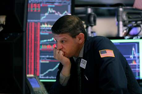 There is a moral question over how society should handle the pandemic and how that relates to the health of the economy and workers. A trader is photographed at his post on the floor of the New York Stock Exchange on March 11.