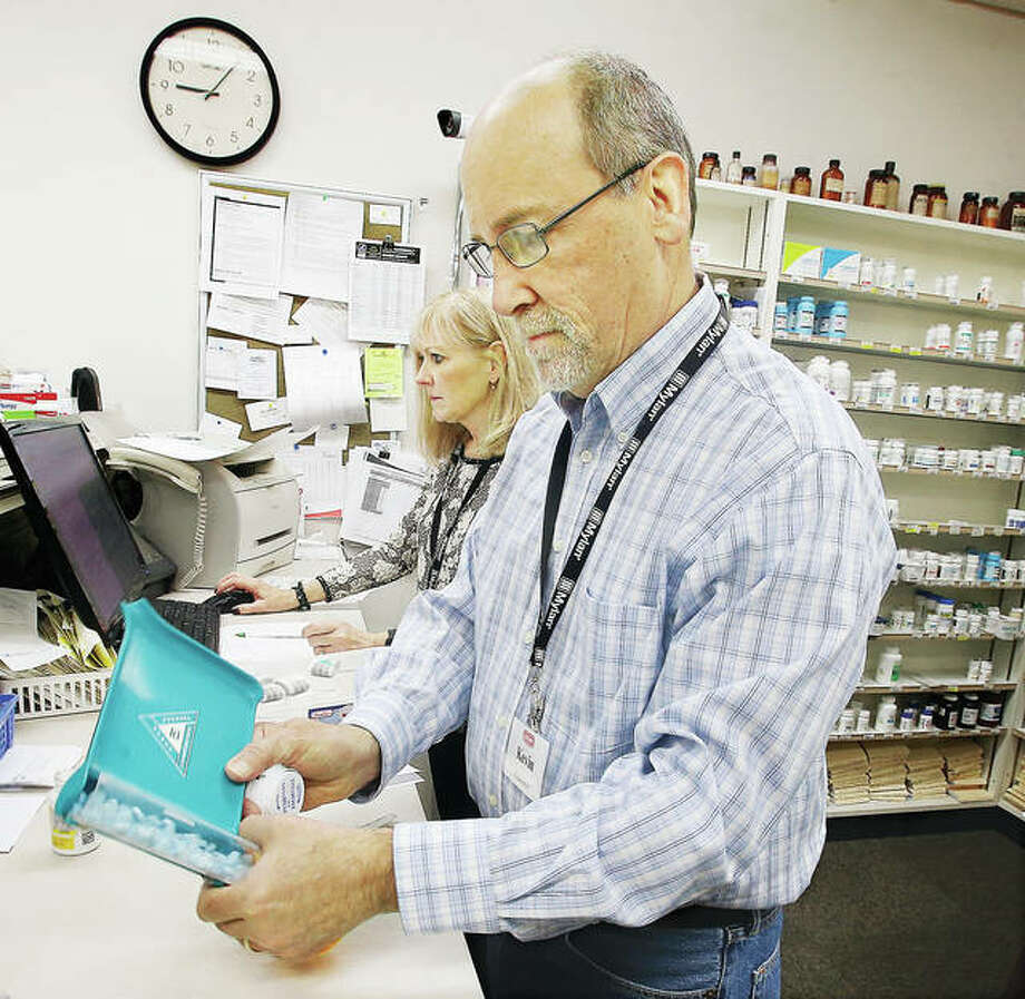 Kevin Hendrick and his wife, Valarie, work on filling prescriptions Thursday at Camp Drug Store located at the corner of Ferguson Avenue and 6th Street in Wood River. Pharmacies are considered essential businesses, and locally owned pharmacies in the area are doing their part to keep the state moving through the COVID-19 virus threat.