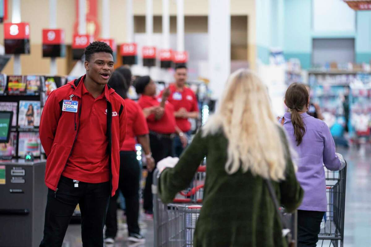 Kevon Adewole, 17, a cashier and bagger at H-E-B, welcomes customers as they enter the store as the doors open Wednesday morning, March 25, 2020, at H-E-B in Bellaire.