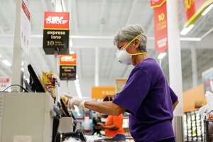 Connie Herring wears a gloves and mask as she uses the self check out line, Wednesday, March 25, 2020, at H-E-B in Bellaire. Herring said she started wearing a mask in public about a week ago. Her husband had a a major surgery two weeks ago, and she does not want to bring anything home with her, she said.