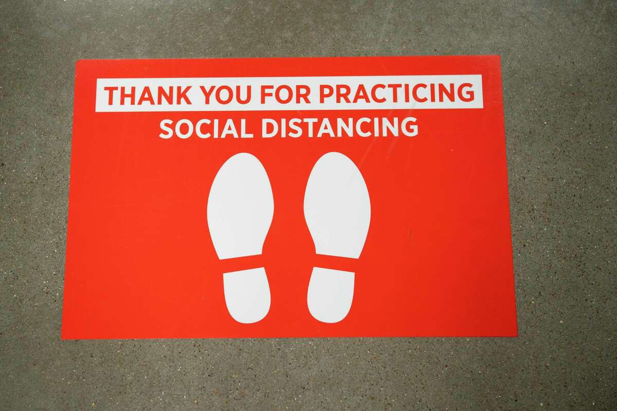Signs remind customers to practice social distancing while waiting in line, Wednesday, March 25, 2020, at H-E-B in Bellaire.