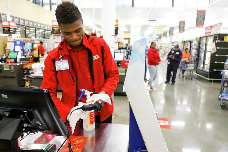 Kevon Adewole, 17, a cashier and bagger at H-E-B, sanitizes a self check out register after a customer used it, Wednesday, March 25, 2020, at H-E-B in Bellaire. Photo: Mark Mulligan, Houston Chronicle / Staff Photographer / © 2020 Mark Mulligan / Houston Chronicle