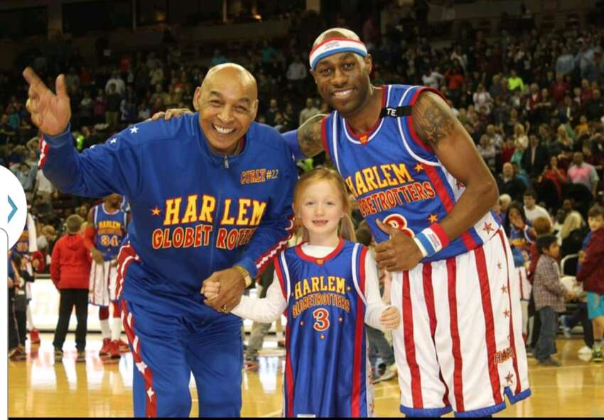 Tay Fisher, right, posing with a young fan, said Harlem Globetrotters great Curly Neal made him a better person. (Courtesy of Tay Fisher)