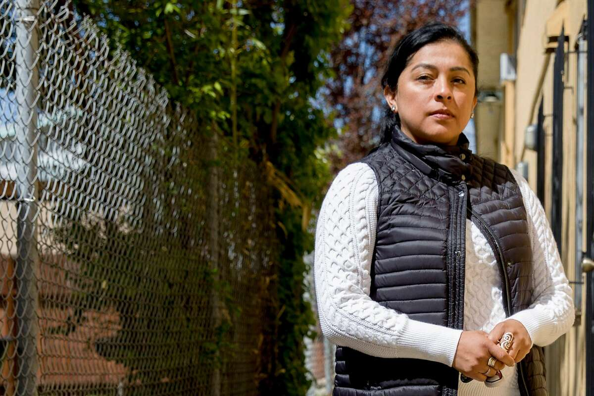 Ivonne Ortez poses for a portrait outside of her home in Oakland, Calif. Thursday, March 26, 2020. Ortez was laid off from her job as a janitor at the Oakland Coliseum. She has a second job cleaning a Berkeley office building, but those hours have been cut.
