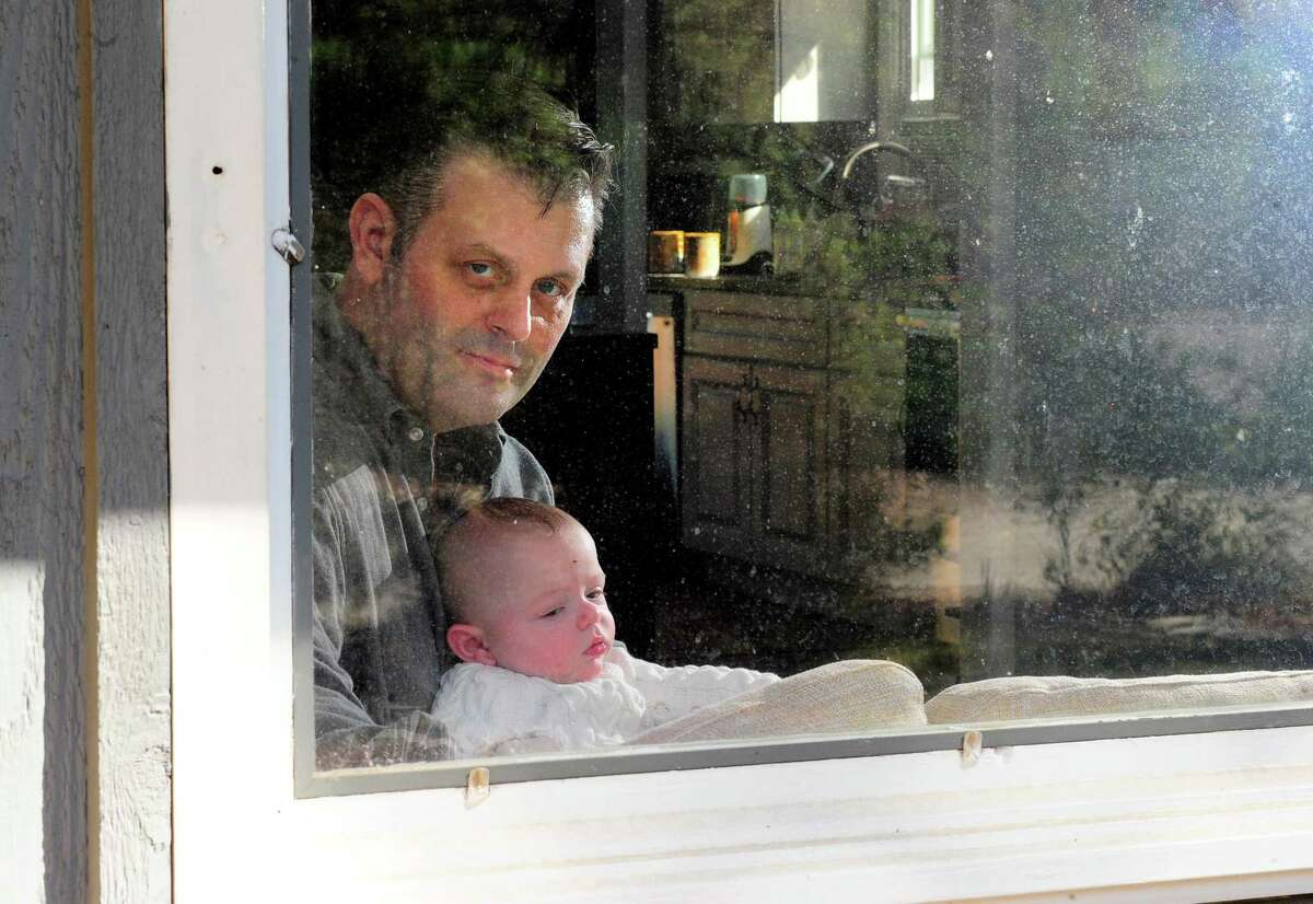 Chris Tillett poses with his son John at his home in Wilton, Conn., on Thursday Mar. 26, 2020. Doctors say Tillett, who was the first coronavirus patient in Connecticut, is no longer contagious and is able to be close with his family again.