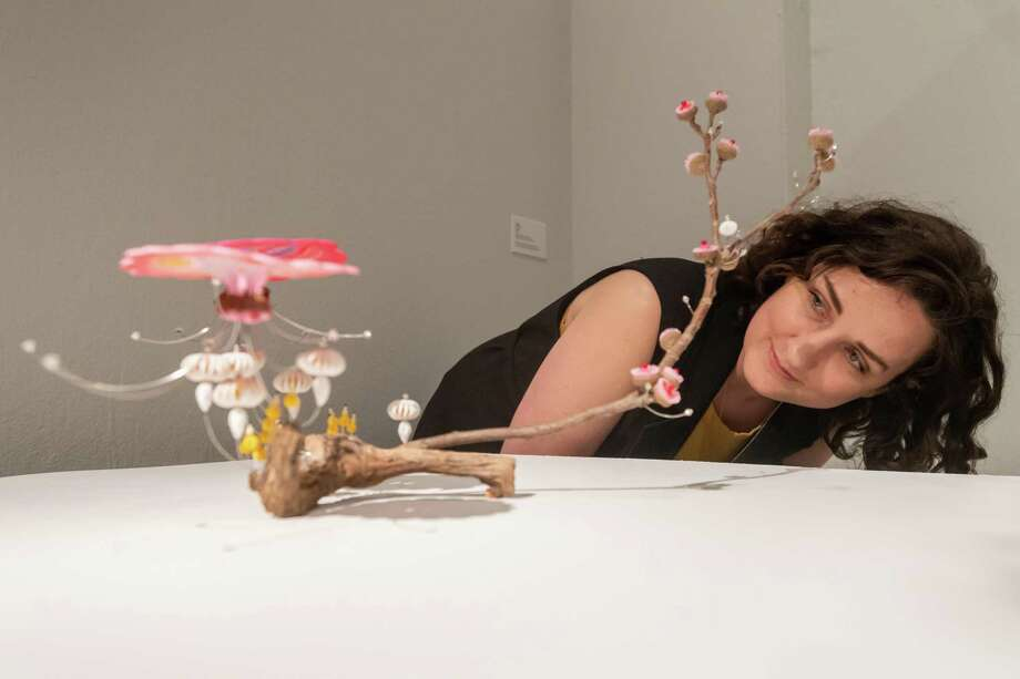 Mariah Rockefeller, Curator of Exhibitions & Collections at the Art Museum of Southeast Texas  takes a closer look at an art piece in Kana Harada's Celestial Garden collection. Photographed on March 20, 2020. Fran Ruchalski/The Enterprise Photo: Fran Ruchalski/The Enterprise / 2019 The Beaumont Enterprise