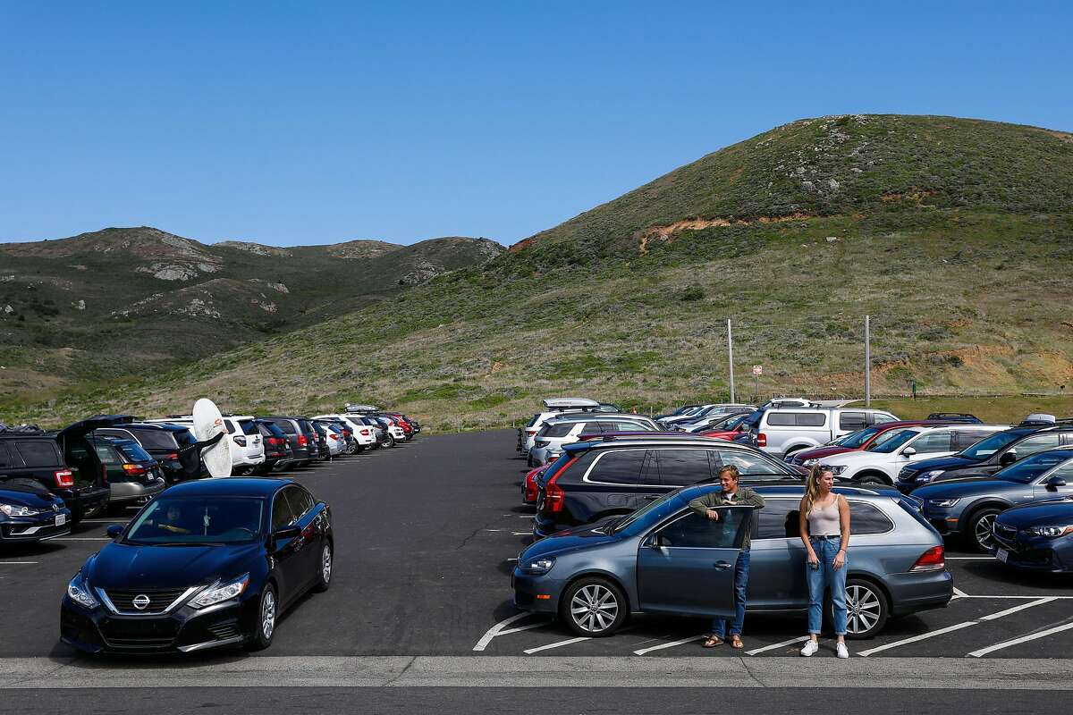 People in the parking lot at Rodeo Beach during the shelter-in-place orders on Sunday, March 22, 2020 in Marin County, California. Many surfers went out because they were concerned that beaches would soon be closed.