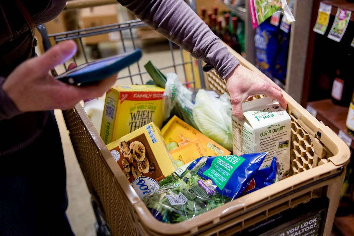 Grocery delivery shopper Courtney Fox of Newark stands in the checkout line as she purchases groceries for three separate Instacart orders at Safeway in Palo Alto, Calif. Tuesday, March 17, 2020.Instacart classifies shoppers for the service as independent contractors.