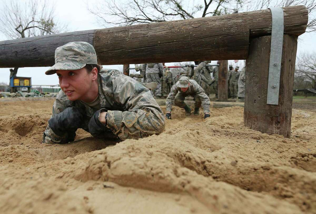 An Air Force basic trainee crawls in sand under an obstacle at Joint Base San Antonio-Lackland in 2018. Coronavirus concerns have prompted commanders to prepare an alternate training site at Keesler AFB in Biloxi, Mississippi, to open April 7. (Kin Man Hui/San Antonio Express-News)