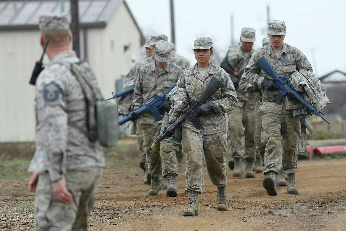 Air Force basic trainees march with mock M-16s to the next obstacle at Joint Base San Antonio-Lackland in 2018. Coronavirus concerns have prompted commanders to prepare an alternate training site at Keesler AFB in Biloxi, Mississippi, to open April 7. (Kin Man Hui/San Antonio Express-News)