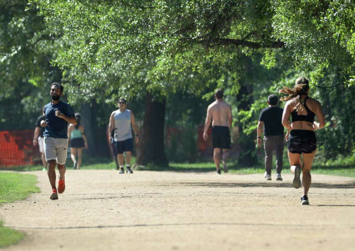 People run in Memorial Park on Wednesday, March 25, 2020, in Houston. The City of Houston and Harris County officials instituted a stay-at-home order at 11:59 p.m. the previous night, due to concerns about COVID-19.