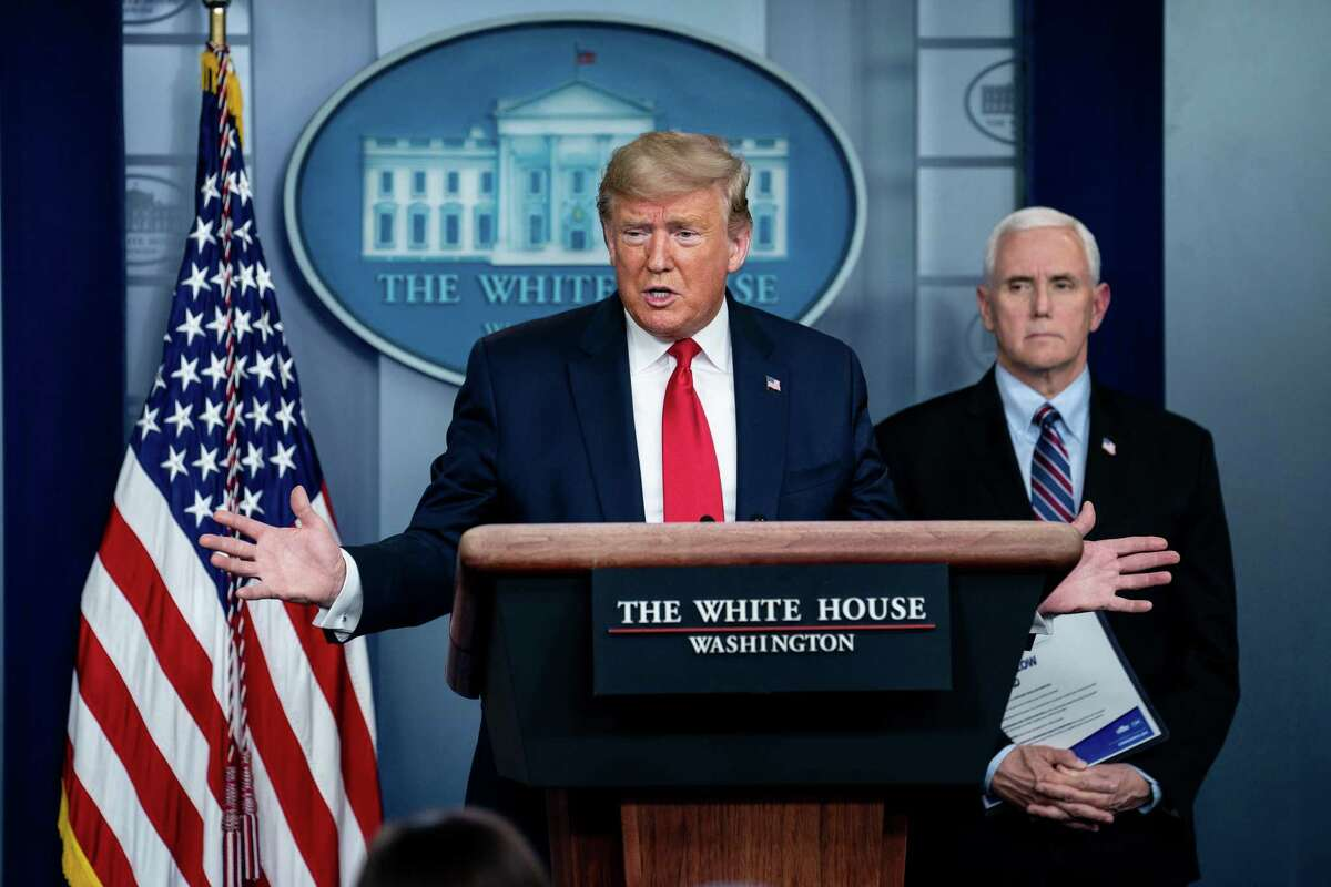 President Donald Trump speaks about the coronavirus, while Vice President Mike Pence listens, during a task force news conference at the White House in Washington, March 26, 2020. (Erin Schaff/The New York Times)