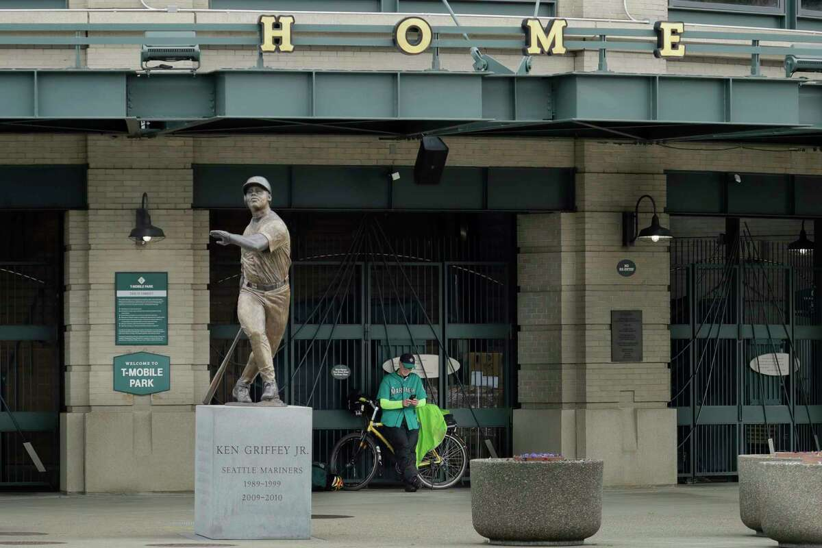 Al Jackson, a die-hard Seattle Mariners fan and 11-year season ticket holder, leans against the gate at the home plate entrance near the Ken Griffey Jr. statue at T-Mobile Park in Seattle, Thursday, March 26, 2020, around the time when the Mariners' Opening Day baseball game against the visiting Texas Rangers would have started. The Seattle Mariners announced Thursday a partnership with Bloodworks Northwest to ensure blood needs are met in the community during the novel coronavirus pandemic.