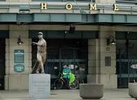 Al Jackson, a die-hard Seattle Mariners fan and 11-year season ticket holder, leans against the gate at the home plate entrance near the Ken Griffey Jr. statue at T-Mobile Park in Seattle, Thursday, March 26, 2020, around the time when the Mariners' Opening Day baseball game against the visiting Texas Rangers would have started. Earlier in the month, Major League Baseball called off the start of the season due to the outbreak of the new coronavirus, but Jackson said he still felt he needed to be down at the ballpark just the same. (AP Photo/Ted S. Warren)