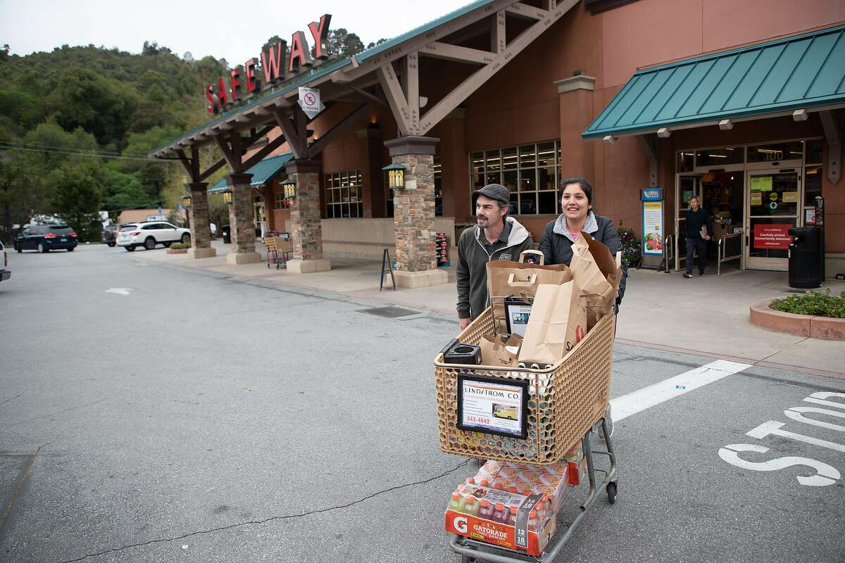 Daniel and Liliana Robertson, of Palo Alto, head to their vehicle after shopping at the Crystal Springs Village Safeway Monday, March 23, 2020, in San Mateo, Calif. Their Palo Alto Safeway didn't have everything they were looking for so they came to the San Mateo store.