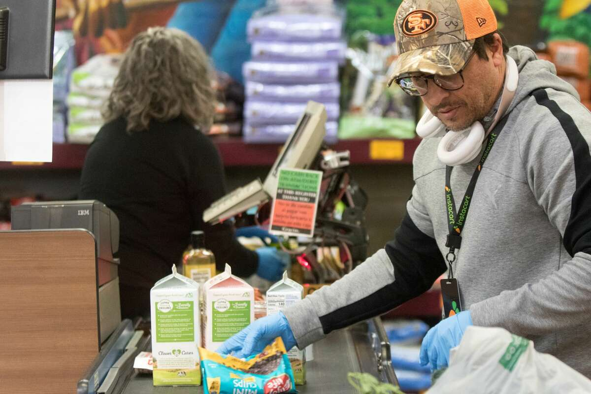 InstaCart shopper Anderson Menezes loads up groceries for purchase at a Rainbow Grocery register. The store has put in limits on the amount of customers inside grocery store to promote social distancing and help prevent the spread of Covid-19 coronavirus in San Francisco, Calif. on March 26, 2020.
