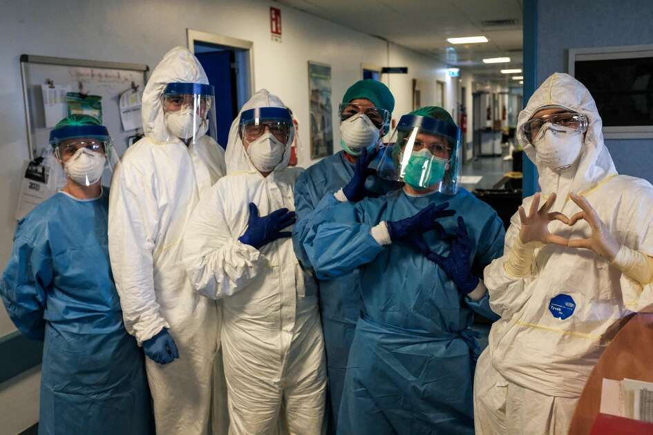 """TOPSHOT - A group of nurses wearing protective mask and gear pose for a group photo prior to their night shift on March 13, 2020 at the Cremona hospital, southeast of Milan, Lombardy, during the country's lockdown aimed at stopping the spread of the COVID-19 (new coronavirus) pandemic. - After weeks of struggle, they're being hailed as heroes. But the Italian healthcare workers are exhausted from their war against the new coronavirus. (Photo by Paolo MIRANDA / AFP) / RESTRICTED TO EDITORIAL USE - MANDATORY CREDIT """"AFP PHOTO / PAOLO MIRANDA"""" - NO MARKETING - NO ADVERTISING CAMPAIGNS - DISTRIBUTED AS A SERVICE TO CLIENTS (Photo by PAOLO MIRANDA/AFP via Getty Images)"""