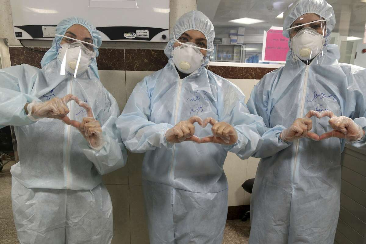 Nurses make a sign of heart with their fingers, in a ward dedicated for people infected with the new coronavirus, at a hospital in Tehran, Iran, Sunday, March 8, 2020.